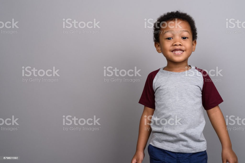 Studio shot of young African boy against gray background stock photo