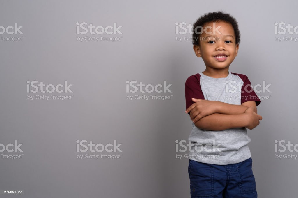 Tiro de estúdio do jovem rapaz Africano contra fundo cinza - foto de acervo