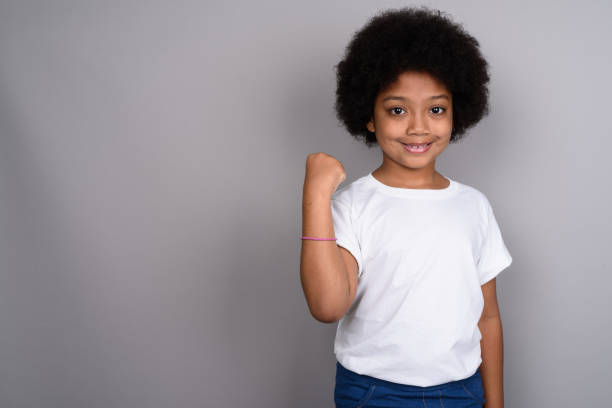 Studio shot of young African girl against gray background stock photo