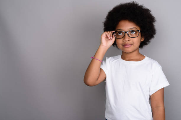 Studio shot of young African girl against gray background Studio shot of young African girl against gray background nerd hairstyles for girls stock pictures, royalty-free photos & images