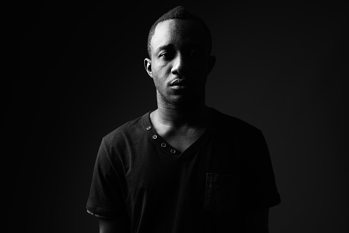Studio shot of young African man wearing black shirt in black and white horizontal shot