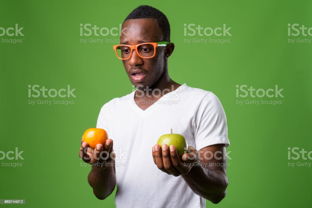 Studio shot of young African man wearing white shirt against green background stock photo