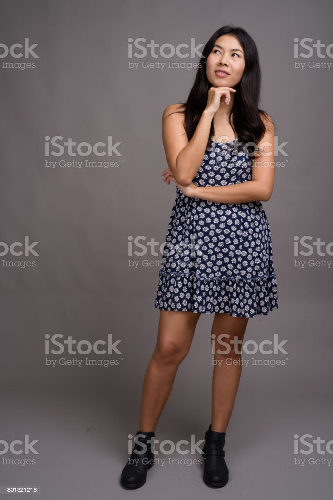 Studio shot of young Asian businesswoman against gray background stock photo