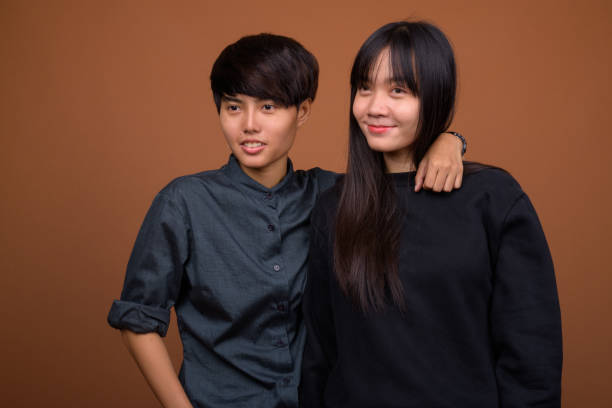 Studio shot of young Asian lesbian couple together and in love against colored background stock photo