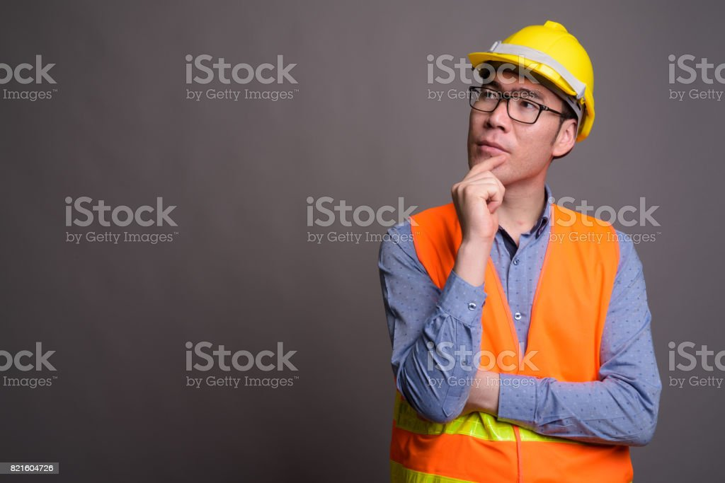 Studio shot of young Asian man construction worker against gray background stock photo