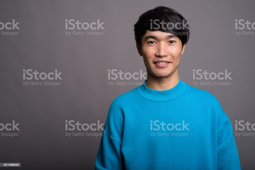 Studio shot of young Asian man wearing blue sweater against gray background stock photo