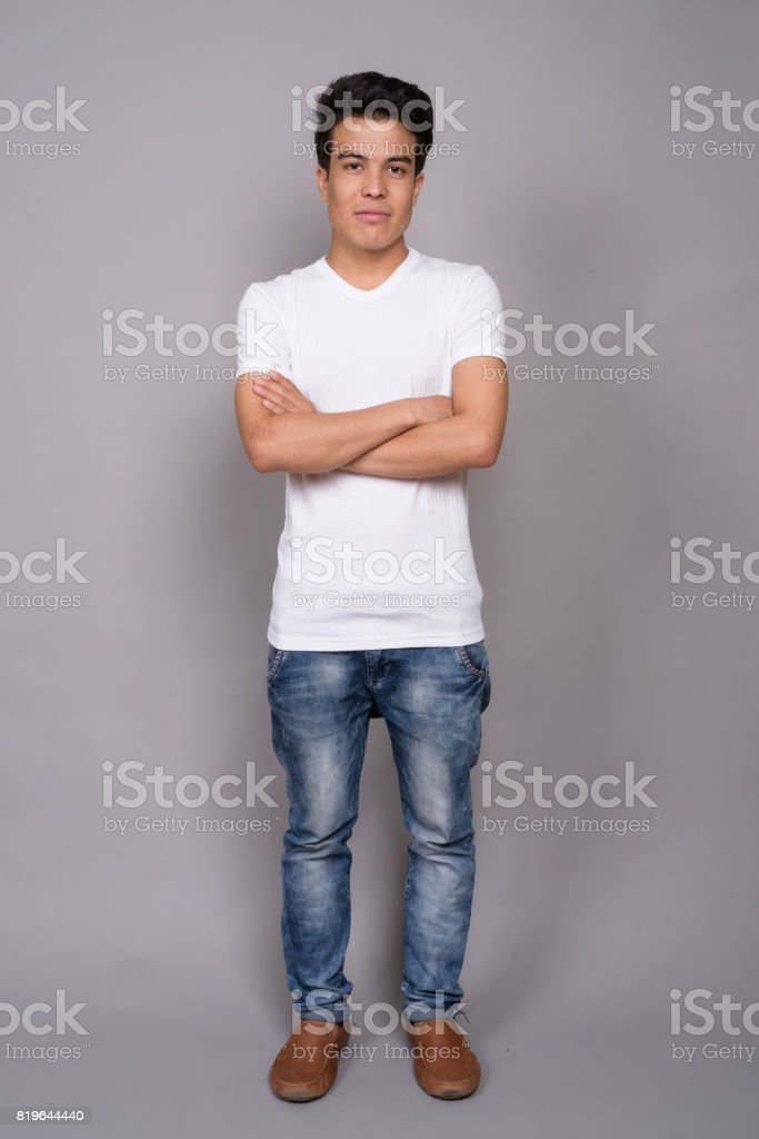 92ae56055160 Studio shot of young Asian man wearing casual clothing against gray  background royalty-free stock
