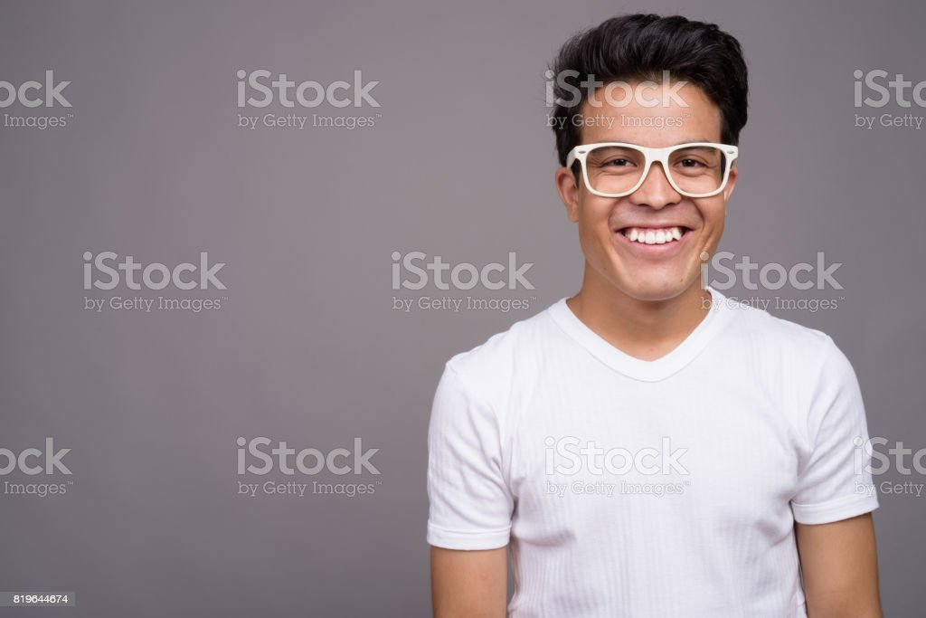 a8bb3ac7de0b Studio shot of young Asian man wearing eyeglasses and casual clothing  against gray background royalty-