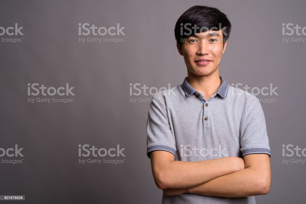 Studio shot of young Asian man wearing gray polo shirt against gray background stock photo