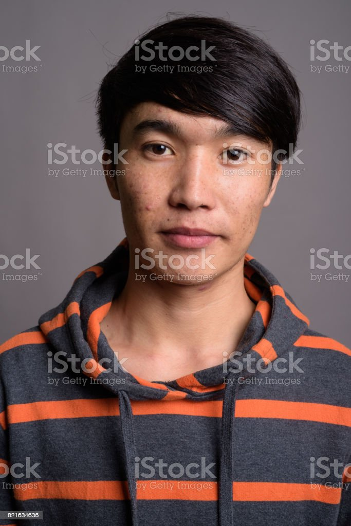 Studio shot of young Asian man wearing hoodie against gray background stock photo
