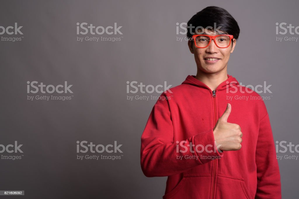 fc058712bca5 Studio shot of young Asian man wearing red jacket matching with red eyeglasses  against gray background - Stock image .