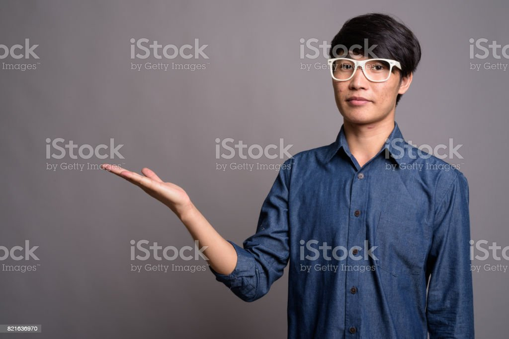 1e2be131526e Studio shot of young Asian man wearing smart casual clothes and eyeglasses  against gray background royalty