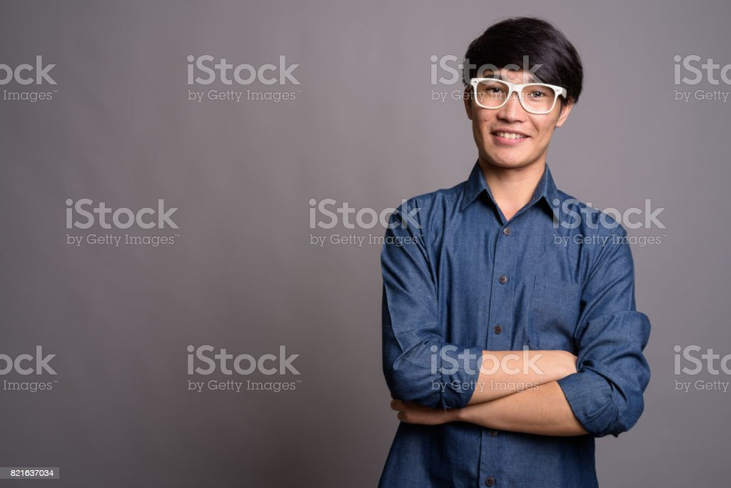 Studio shot of young Asian man wearing smart casual clothes and eyeglasses against gray background stock photo