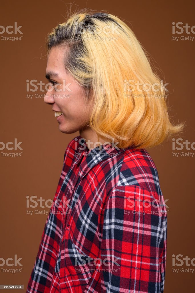 Studio shot of young Asian man wearing stylish clothes against colored background stock photo