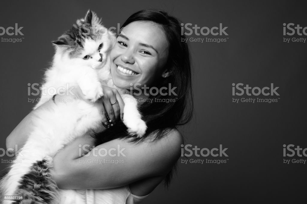 Studio shot of young Asian woman against gray background in black and white stock photo