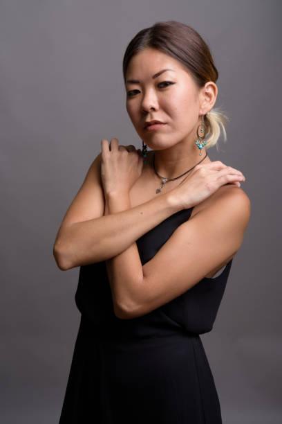 Photo de Studio de jeune femme asiatique vêtue d'une robe noire officielle sur fond gris - Photo
