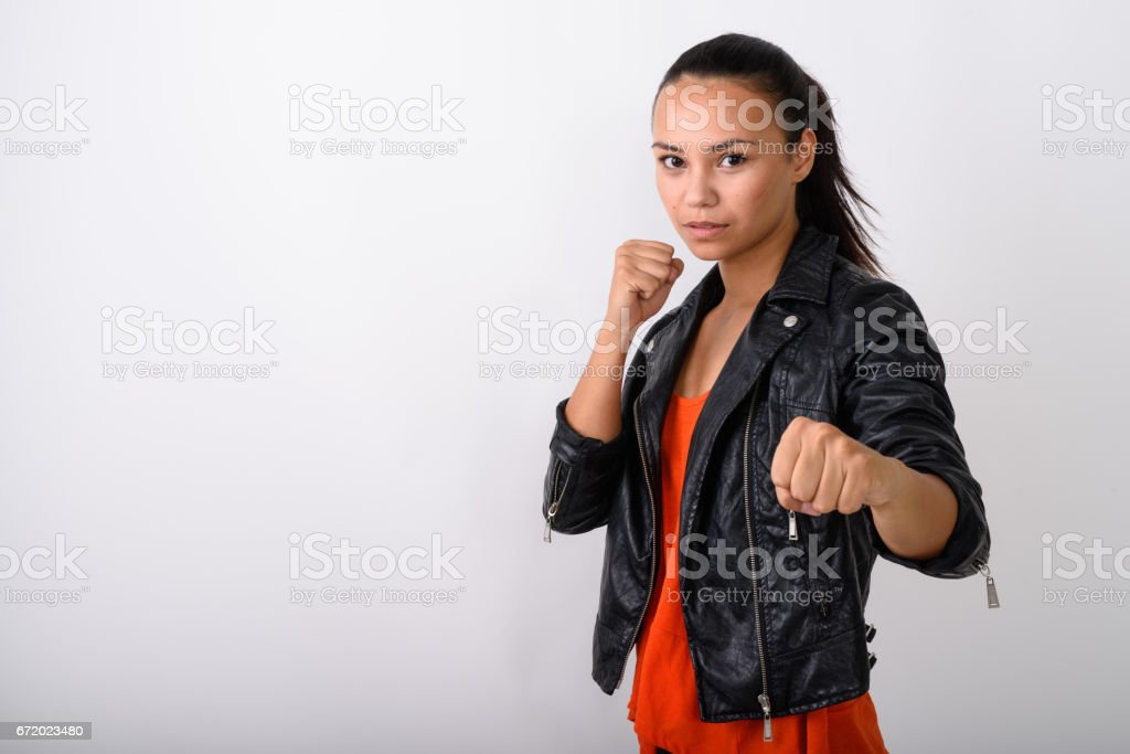 Studio shot of young Asian woman wearing leather jacket ready to fight against white background stock photo
