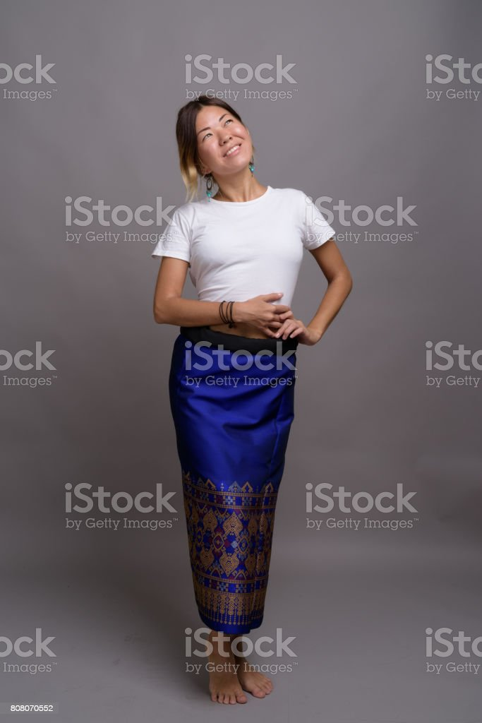 Studio shot of young Asian woman wearing white shirt and traditional skirt against gray background stock photo