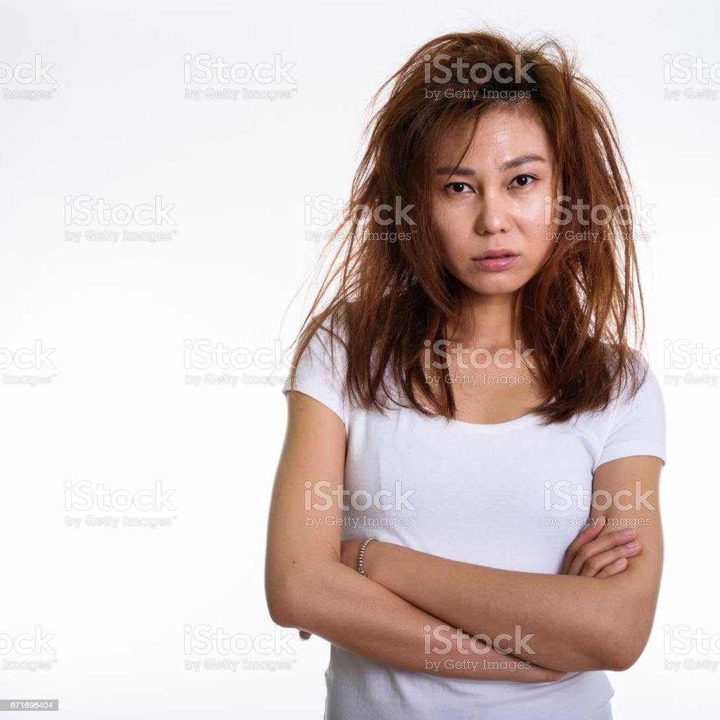 Studio shot of young Asian woman with arms crossed and messy hair against white background stock photo