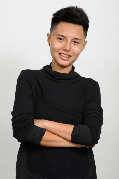 Studio shot of young Asian woman with short hair against white background Studio shot of young Asian woman with short hair against white background vertical shot transgender stock pictures, royalty-free photos & images