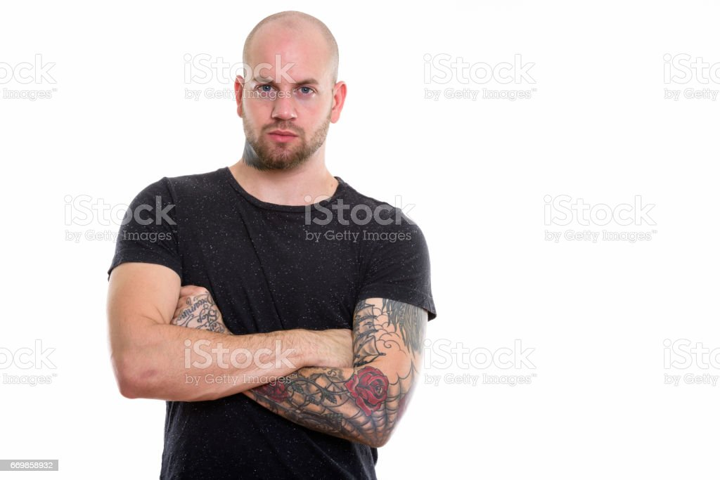 Studio shot of young bald muscular man with tattoos and arms crossed stock photo