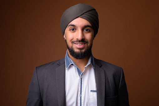 Studio shot of young bearded Indian businessman wearing suit and turban against colored background horizontal shot