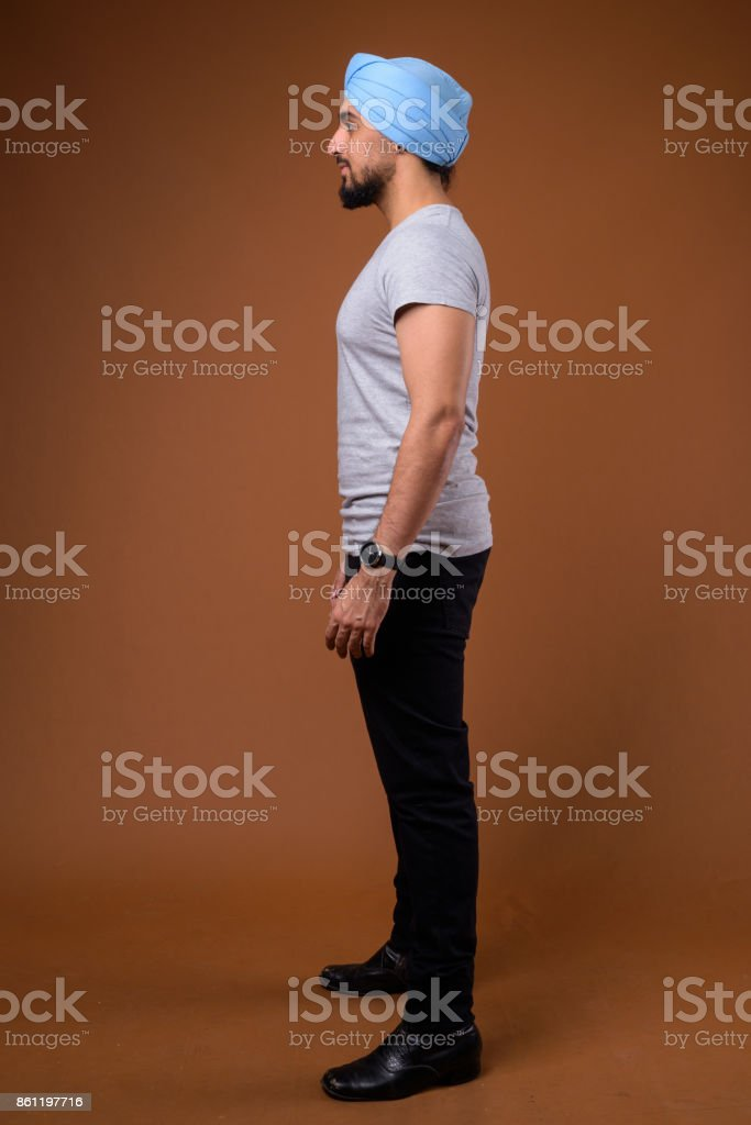 Studio shot of young bearded Indian man wearing casual clothing with blue turban against colored background stock photo