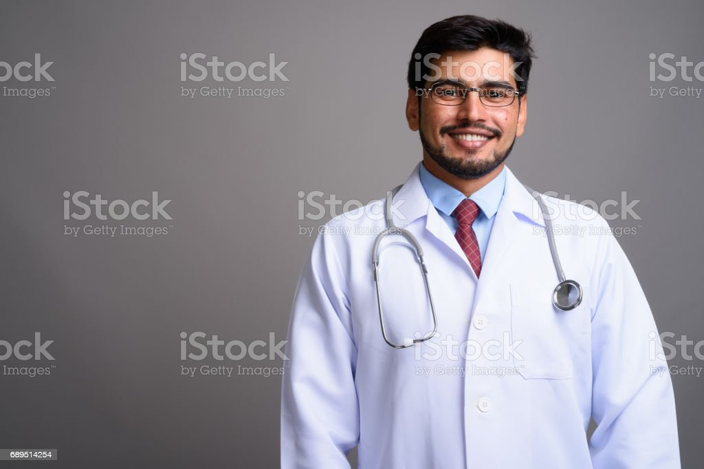 Studio shot of young bearded Persian man doctor against gray background stock photo