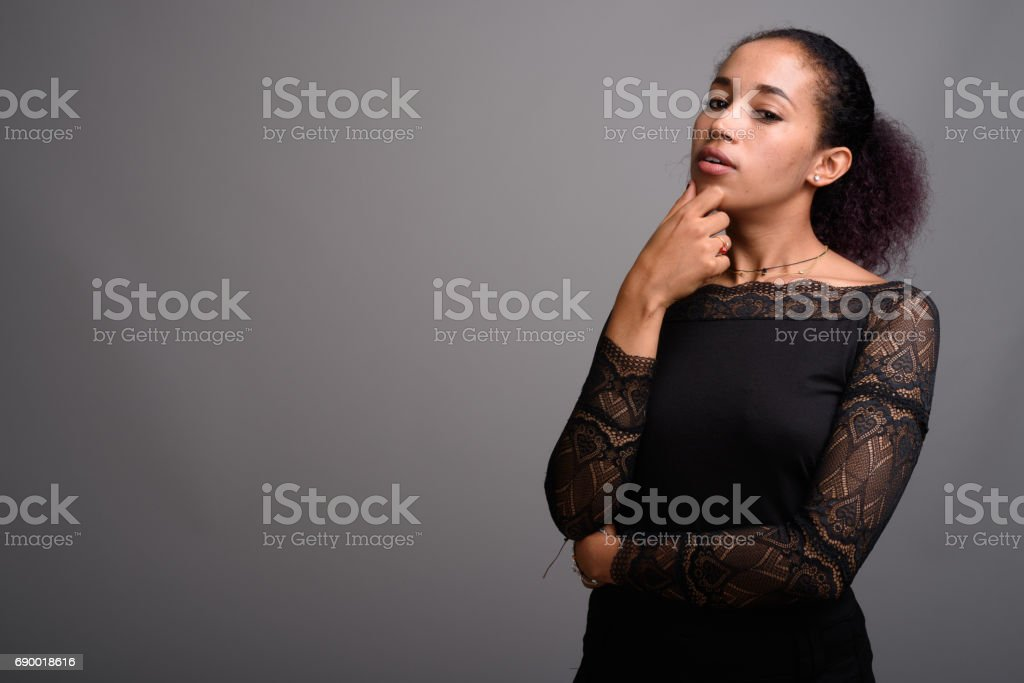 Studio shot of young beautiful African woman against gray background stock photo