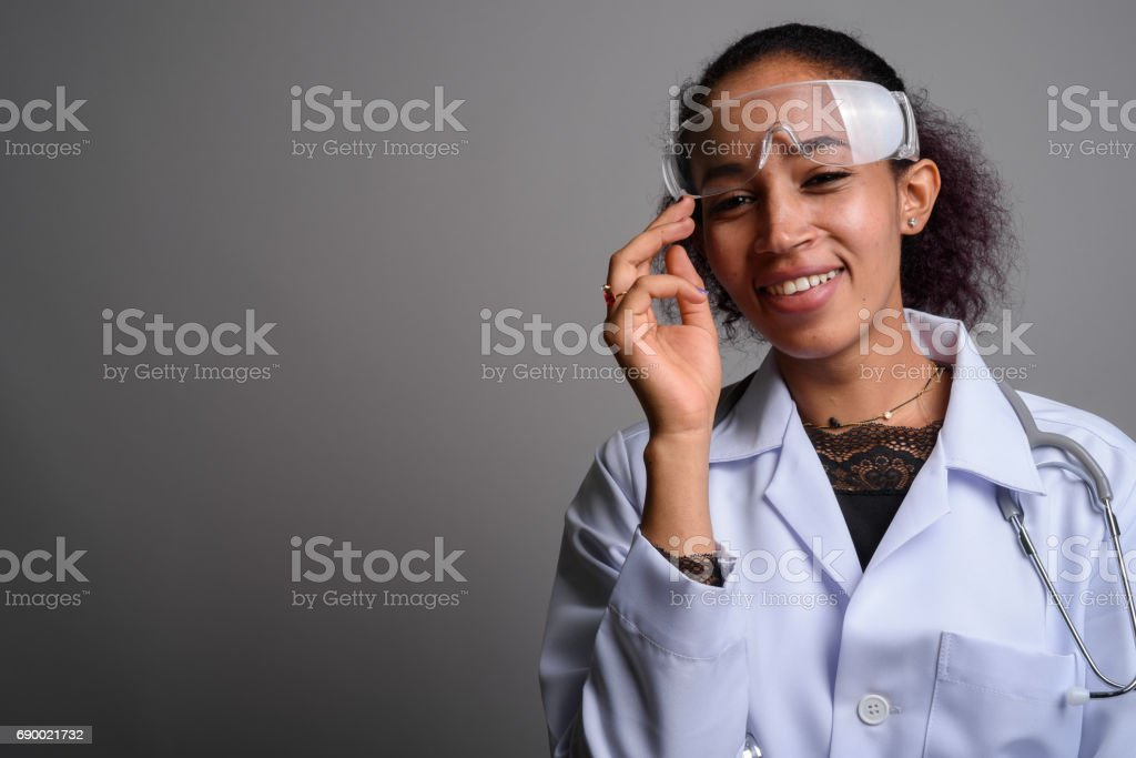 Studio shot of young beautiful African woman doctor against gray background stock photo