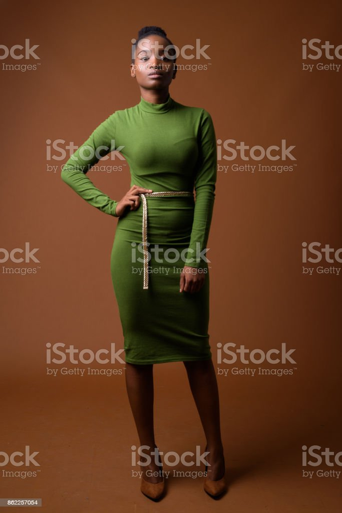 Studio shot of young beautiful African Zulu businesswoman wearing green outfit against colored background stock photo