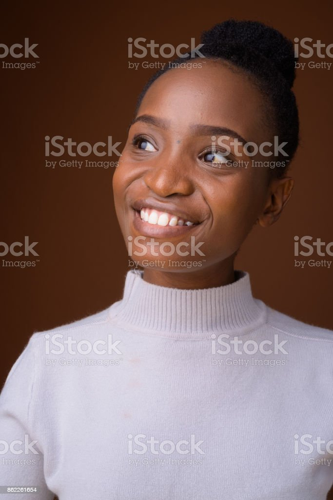 Studio shot of young beautiful African Zulu businesswoman wearing white turtleneck sweater against colored background stock photo
