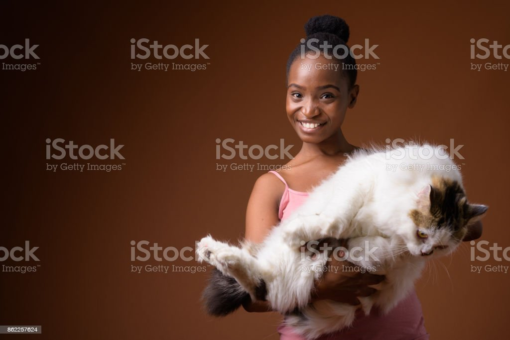 Studio shot of young beautiful African Zulu woman holding cute cat against colored background stock photo