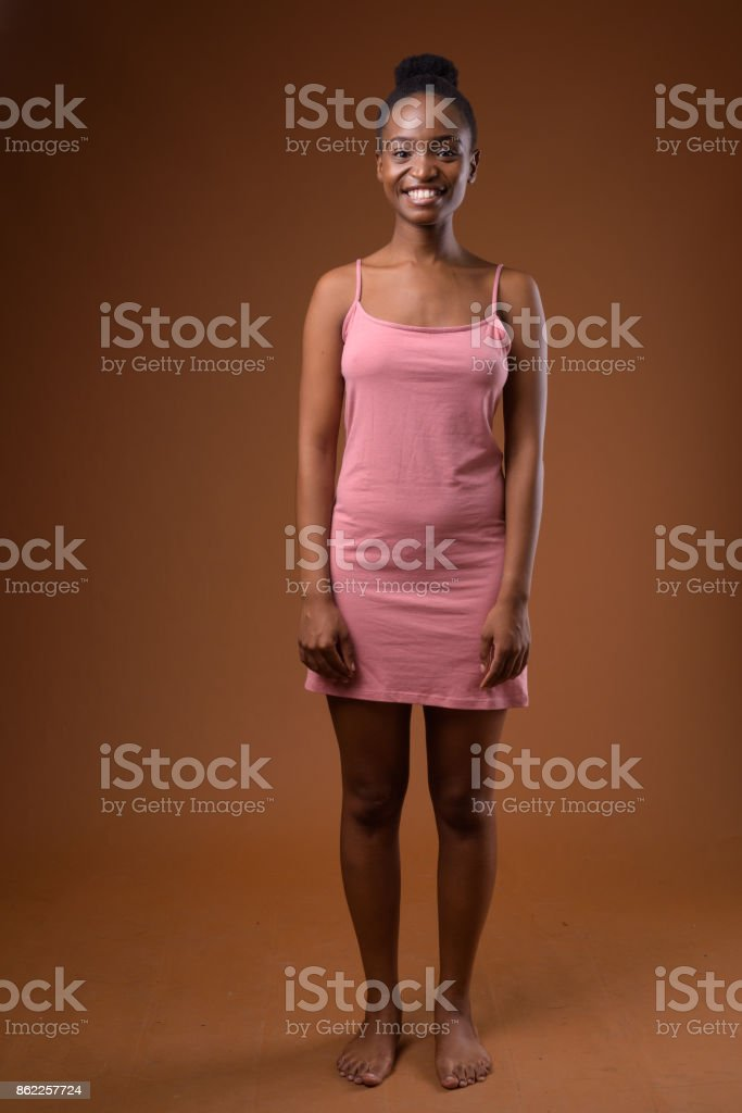 Studio shot of young beautiful African Zulu woman wearing pink sleeveless dress against colored background stock photo