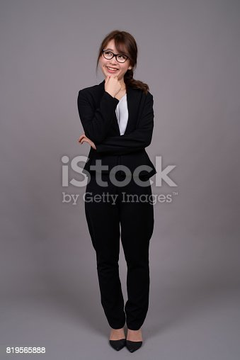 618976144 istock photo Studio shot of young beautiful Asian businesswoman against gray background 819565888