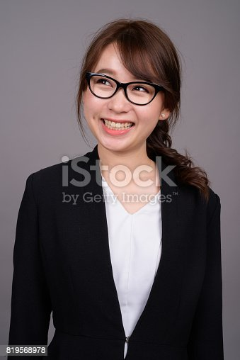618976144 istock photo Studio shot of young beautiful Asian businesswoman against gray background 819568978