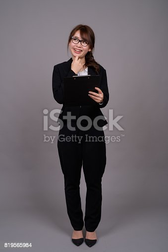 618976144 istock photo Studio shot of young beautiful Asian businesswoman holding clipboard against gray background 819565984
