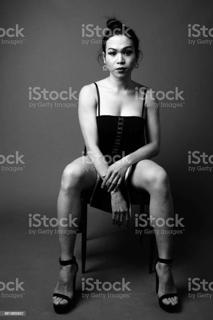 2ef60cfd0a Studio shot of young beautiful Asian transgender woman sitting on chair in  black and white - Stock image .
