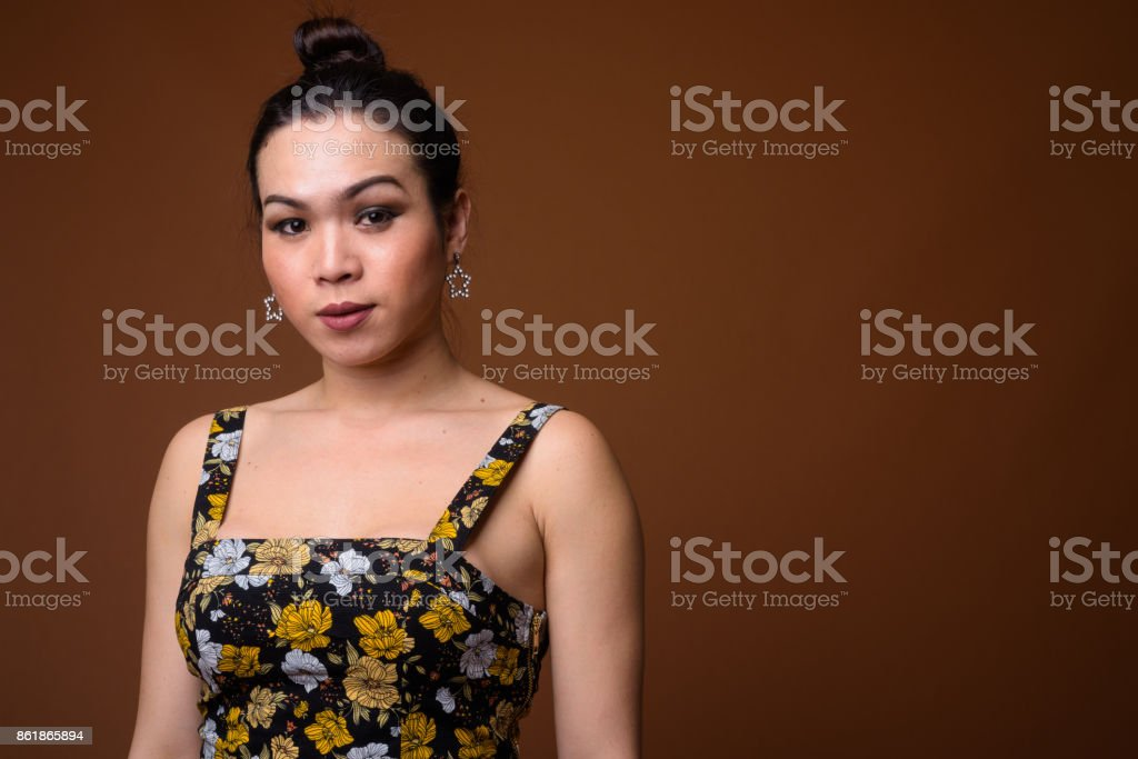 Studio shot of young beautiful Asian transgender woman with hair tied up against colored background stock photo