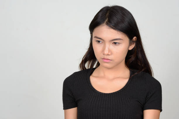 Studio shot of young beautiful Asian woman wearing black shirt against white background Studio shot of young beautiful Asian woman wearing black shirt against white background horizontal shot sad asian woman stock pictures, royalty-free photos & images