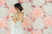 Studio shot of young beautiful bride on background of flowers. Professional make-up and hairstyle.