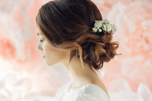 Studio shot of young beautiful bride on background of flowers. Professional make-up and hairstyle