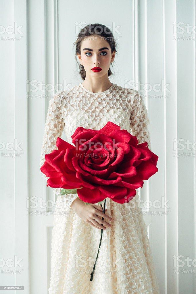 Studio shot of young beautiful bride with big rose stock photo