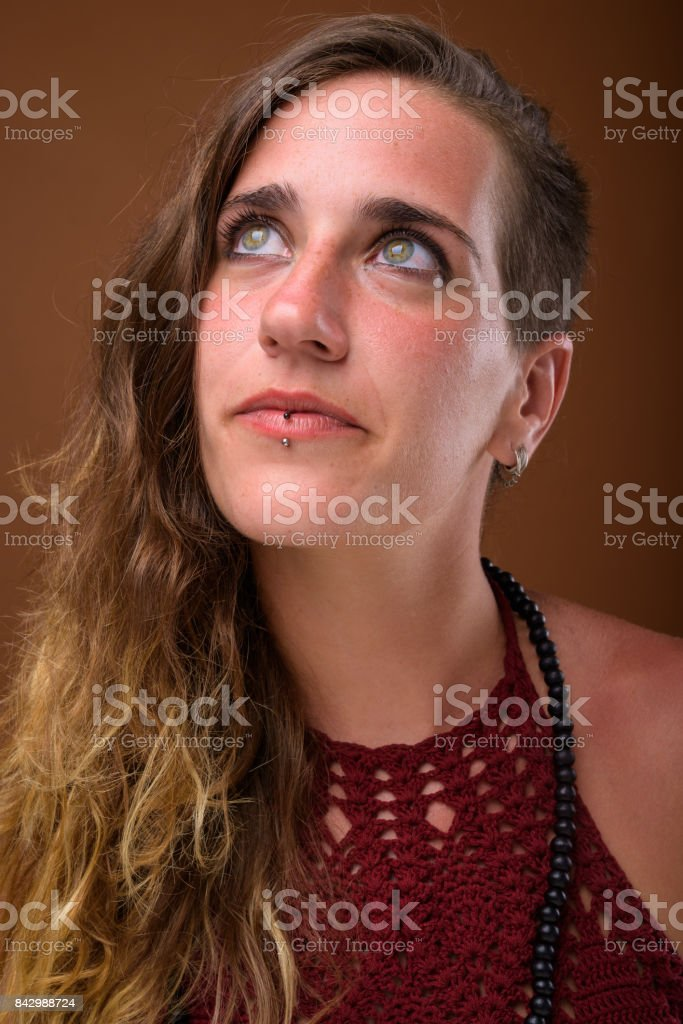 Studio shot of young beautiful Hispanic woman against colored background stock photo