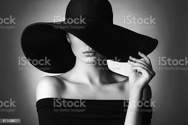 Studio shot of young beautiful woman wearing hat on dark background