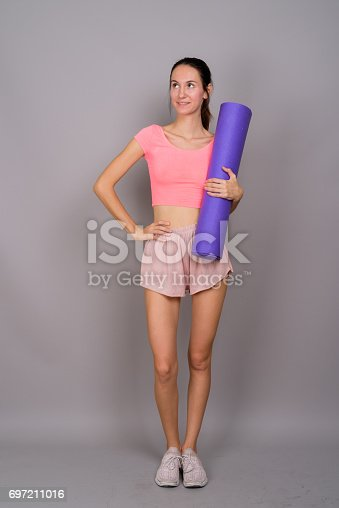 Studio shot of young beautiful woman ready for gym against gray background vertical shot