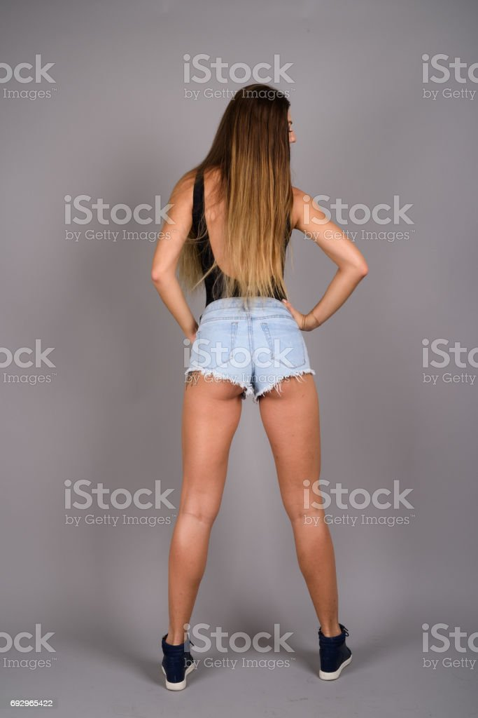 Studio shot of young beautiful woman wearing denim shorts and sleeveless top against gray background stock photo