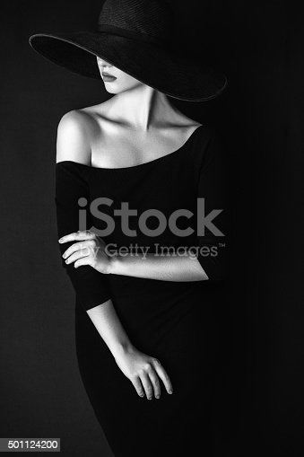 Studio shot of young beautiful woman wearing hat on dark background