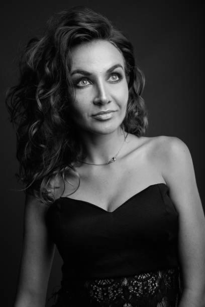 studioaufnahme der junge schöne frau mit lockigem haar tragen schwarze kleid vor grauem hintergrund - k projekt stock-fotos und bilder