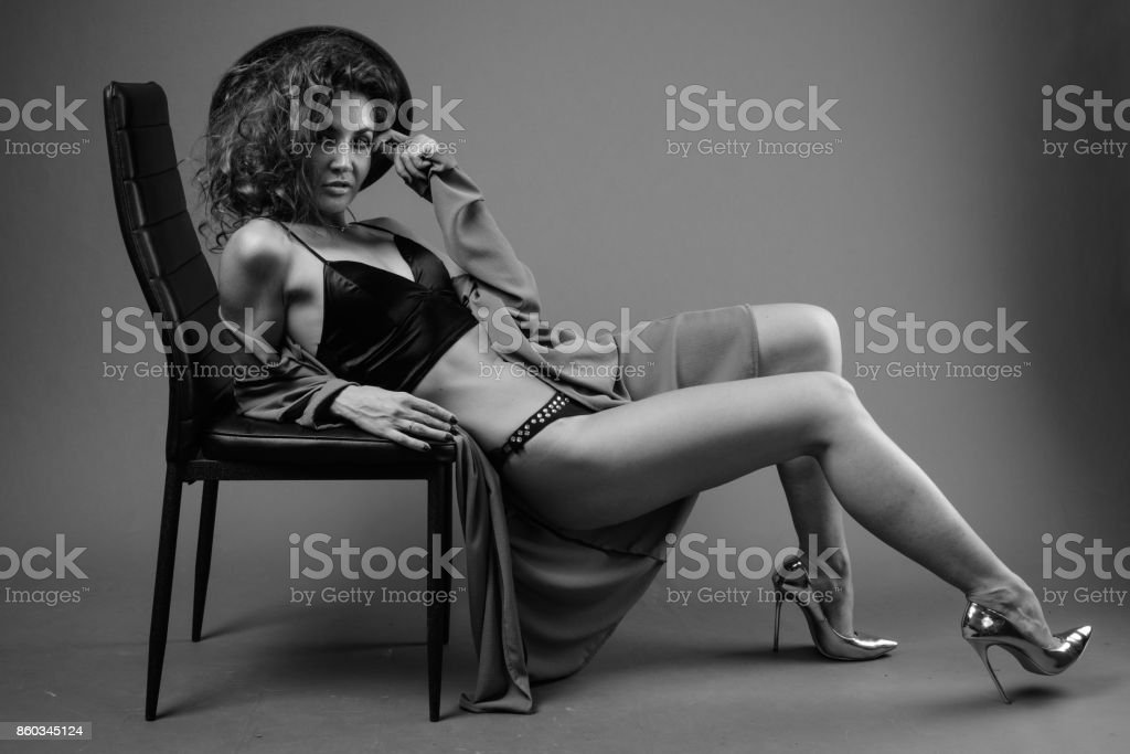 Studio shot of young beautiful woman with curly hair wearing lingerie under long coat against gray background stock photo